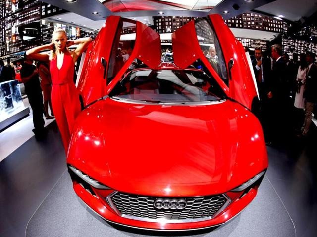 A hostess stands next to an Audi Nanuk Quattro during the first press day of the 65th Frankfurt Auto Show in Frankfurt, Germany. (AP Photo)
