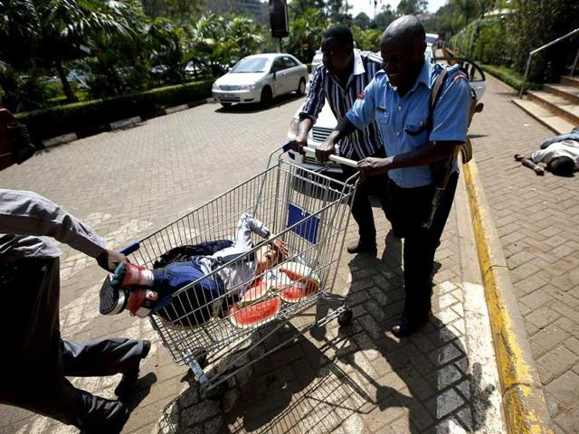 Security forces push an injured person in a shopping trolley past the body of a man from the Westgate shopping centre as police search for gunmen in Nairobi. (Reuters Photo)
