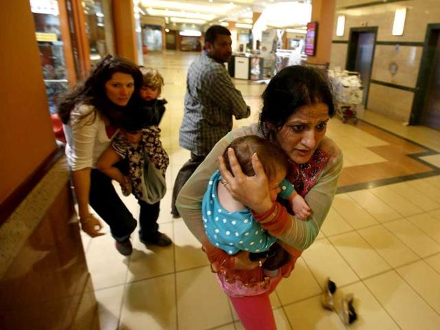 Women carrying children run for safety as armed police hunt gunmen who went on a shooting spree in Westgate shopping centre in Nairobi, Kenya. (Reuters Photo)