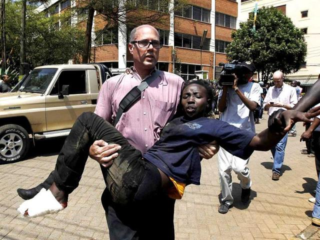 A journalist rescues a woman injured in a shootout between armed men and the police at the Westgate shopping mall in Nairobi, Kenya. (Reuters Photo)