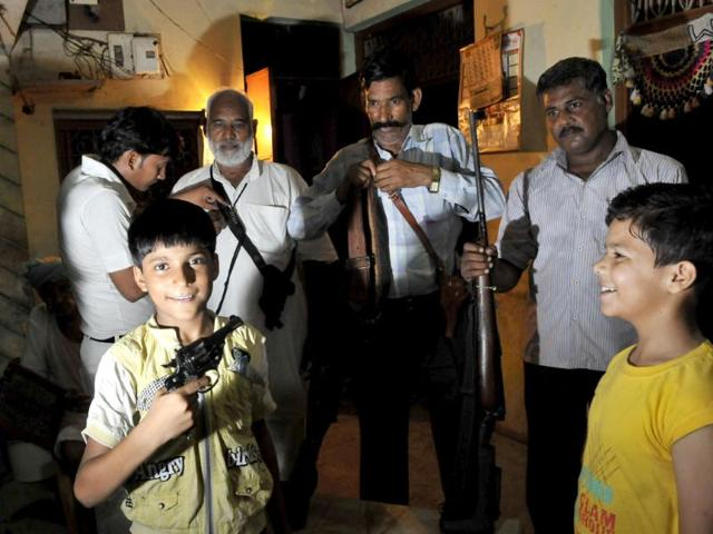 Guns are a matter of pride and not just protection in Uttar Pradesh. In this picture, a family in a village near Etah flaunt rifles and revolvers at their home. Children get a chance to hold weapons too. (Vipin Kumar/ HT photo)