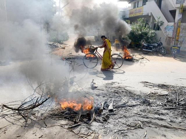 A woman pushes her bicycle through burning barricades set along the road by supporters of united Andhra Pradesh during a protest against the formation of a separate Telangana state. (AFP Photo)