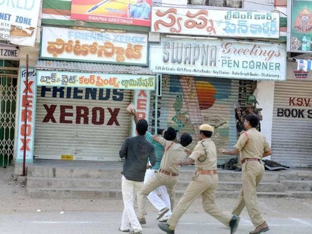 Police detain supporters of united Andhra Pradesh throwing stones at the Congress party office during a protest against the formation of a separate Telangana state, in Ananthapuram. (AFP Photo)