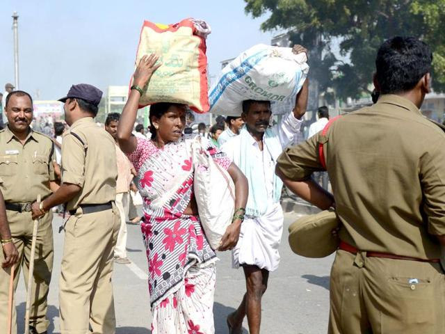 Farmers make their way as police keep watch on supporters of united Andhra Pradesh protesting against the formation of Telangana state, in Ananthapuram. (AFP Photo)