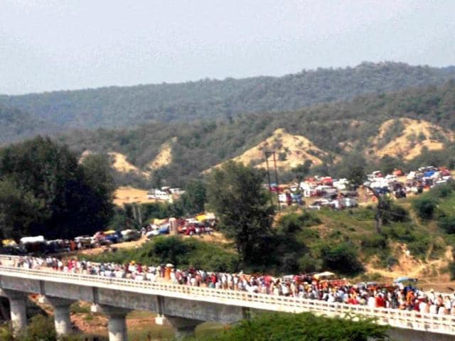 Pilgrims heading towards the Ratangarh temple through the Sindhu River bridge where a stamede took place, in Datia district of Madhya Pradesh on Sunday morning. (PTI Photo)