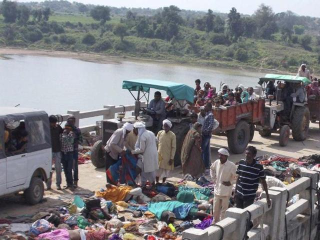 Villagers on tractors move past bodies of victims of a stampede on a bridge across the Sindh River in Datia district in Madhya Pradesh state. (AP Photo)