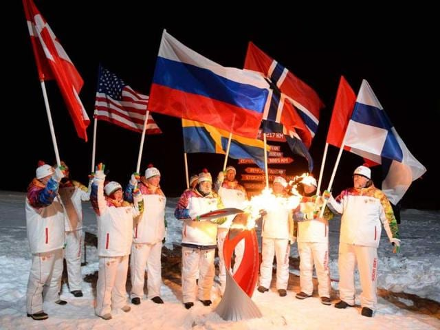 A-group-of-torch-bearers-hold-various-countries-national-flags-and-an-Olympic-torch-at-the-North-Pole-Arctic-Ocean-AP-photo