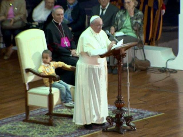 In-this-image-taken-from-TV-footage-taken-on-Saturday-Oct-26-2013--a-young-boy-no-name-available-sits-in-the-chair-of-Pope-Francis-as-he-delivers-his-speech-during-an-audience-with-families-in-St-Peter-s-Square-gathered-for-the-Pontifical-Council-for-the-Family-s-plenary-assembly-at-the-Vatican-AP-photo