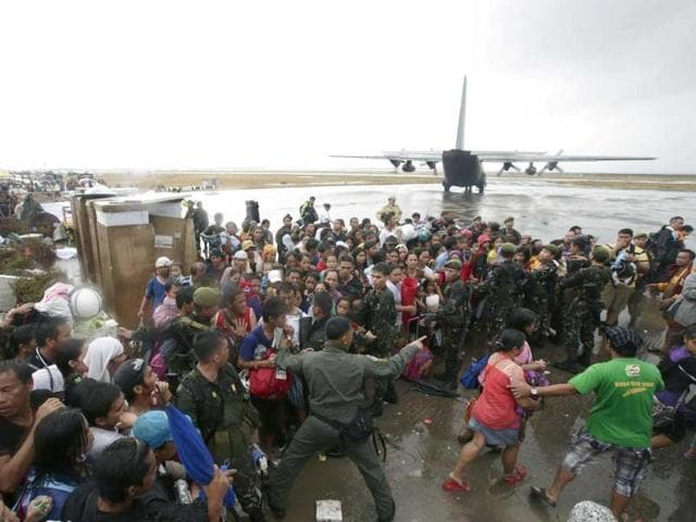Typhoon-survivors-rush-to-get-a-chance-to-board-a-C-130-military-transport-plane-in-Tacloban-city-Leyte-province-central-Philippines-AP-Photo