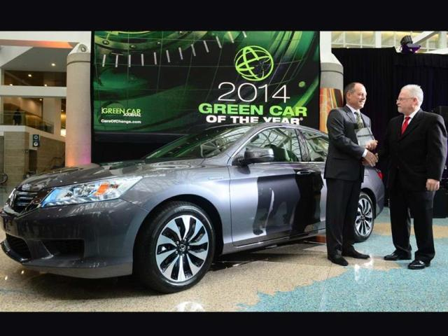 Mike-Accavitti-senior-vice-president-of-Automobile-Operations-at-American-Honda-holds-the-2014-Green-Car-of-the-Year-Award-for-the-2014-Honda-Accord-is-congratulated-by-Ron-Cogan-from-Green-Car-Journal-on-November-21-2013-at-the-LA-Auto-Show-in-Los-Angeles-California-which-opens-to-the-public-from-November-22-to-December-1-Photo-AFP