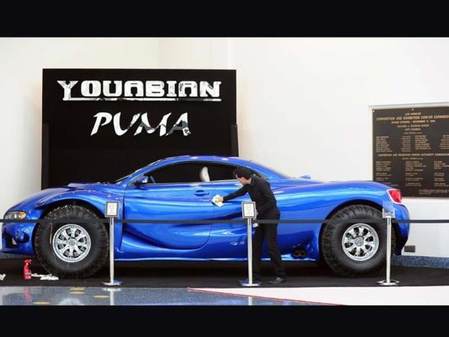 A-worker-wipes-clean-the-door-to-a-Youbian-Puma-on-display-on-November-19-2013-in-Los-Angeles-Photo-AFP