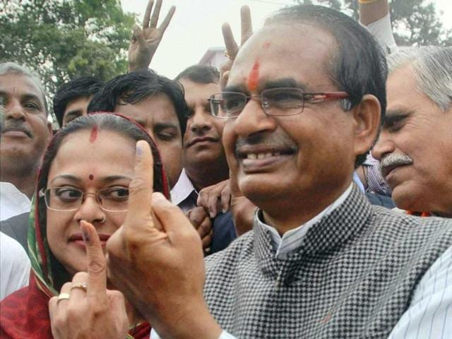 Madhya Pradesh CM Shivraj Singh Chouhan with his wife Sadhna Singh (L) showing their marked fingers after casting votes for Assembly elections in Madhya Pradesh. (PTI)