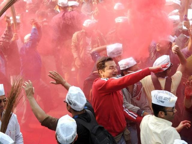 Supporters of AAP celebrate by throwing coloured powder outside their party office in New Delhi. (AFP)