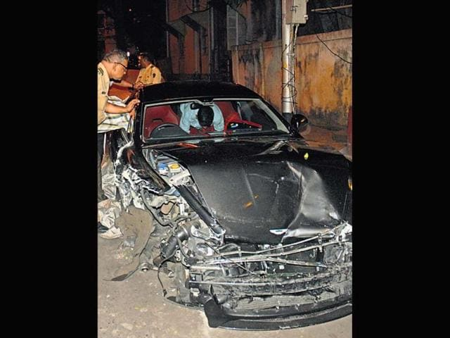 Cops-examine-what-s-left-of-the-Aston-Martin-car-after-the-accident-on-Sunday-HT-photo