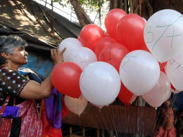 LGBT activists burst balloons during protest against the Supreme Court verdict which validated the section 377 of IPC, in Mumbai. (PTI PHOTO)