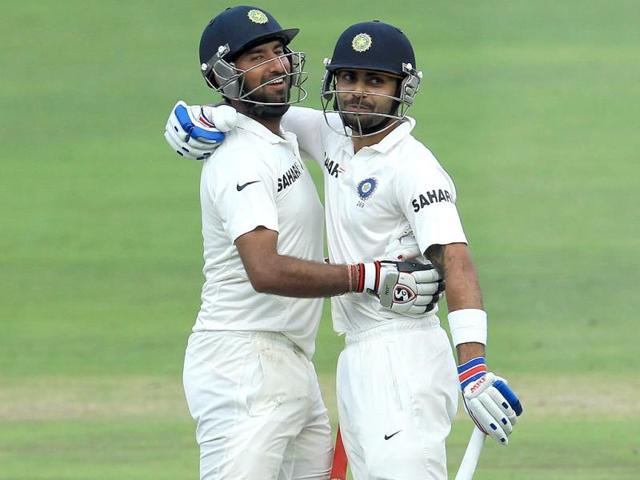 Virat-Kohli-L-watches-as-Cheteshwar-Pujara-R-celebrates-his-century-during-their-2nd-innings-on-the-third-day-of-the-first-Test-match-against-South-Africa-at-the-Wanderers-stadium-in-Johannesburg-AP-Photo