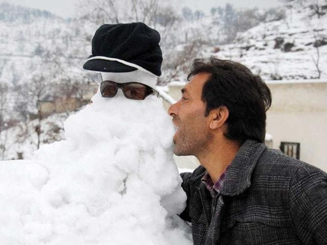 A-man-plays-with-a-snowman-in-Pir-Gali-during-snowfall-in-Poonch-PTI