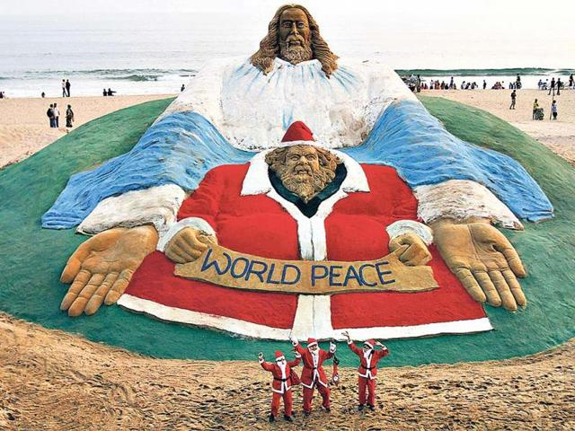 Children-dressed-as-Santa-Claus-dance-in-front-of-a-sculpture-titled-World-Peace-by-sand-artist-Sudarshan-Pattnaik-ahead-of-Christmas-at-a-beach-in-Puri-AP-photo