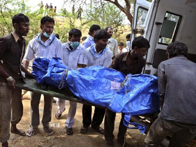 Hospital staff and volunteers load the charred body of a passenger into an ambulance near the site of a train accident at Kothacheruvu, about 155 kilometers north of Bangalore. (AP)