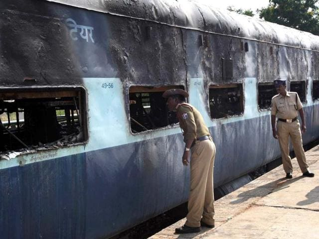 Policemen inspect the charred carriage of the Nanded-Bangalore Express in Puttaparthi in Ananthpur District, some 300kms south of Hyderabad. (AFP)