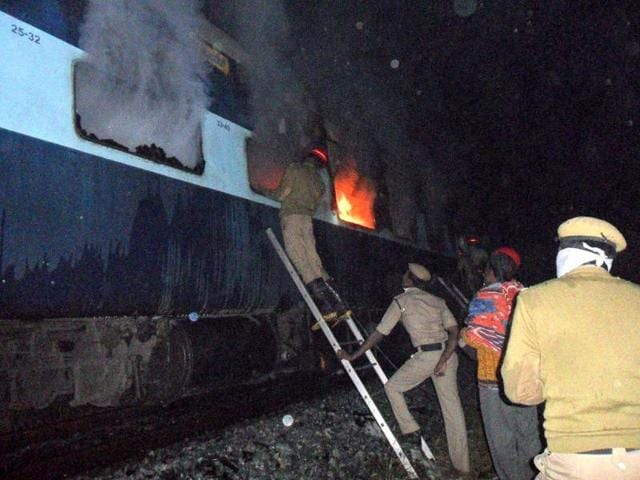 Rescue personnel attempt to open a window of a burning carriage of the Nanded-Bangalore Express near Puttapartihi in Ananthpur District, some 300kms south of Hyderabad. (AFP)