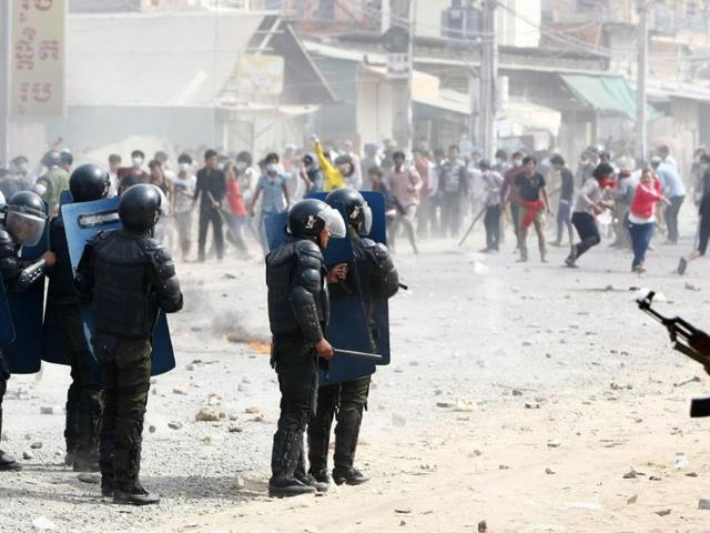 Cambodian-riot-police-with-guns-prepare-to-confront-garment-workers-throwing-stones-and-bricks-near-a-factory-on-the-Stung-Meanchey-complex-on-the-outskirts-of-Phnom-Penh-AP-Photo