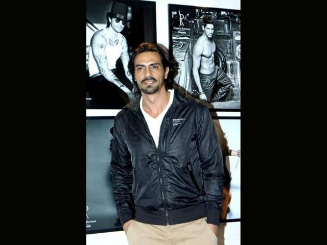 Actor-Arjun-Rampal-poses-in-front-of-calendar-shots-featuring-him-and-Siddharth-Malhotra-Photographer-Daboo-Ratnani-launched-his-calendar-for-2014-featuring-who-s-who-of-Bollywood-on-Sunday-in-Mumbai