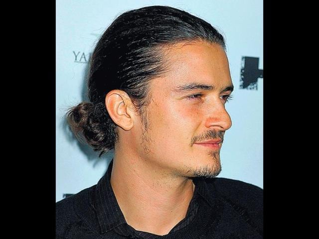 Orlando-Bloom-pulls-back-his-curly-locks-into-a-man-bun