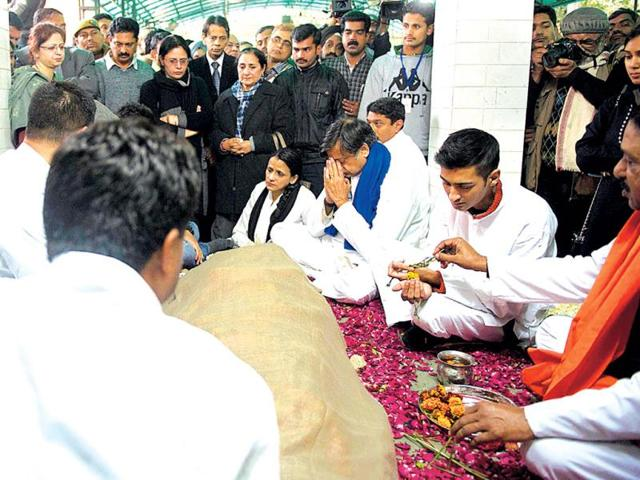 Shashi Tharoor gestures as he sits with other relatives and friends alongside the body of his wife Sunanda Pushkar at a cremation centre in New Delhi. (AFP Photo)