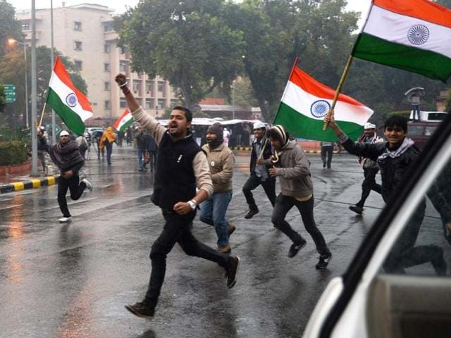 A file photo of AAP supporters carry the Tricolours as they run close to the area where Arvind Kejriwal spent the night during dharna in New Delhi. (AFP photo)