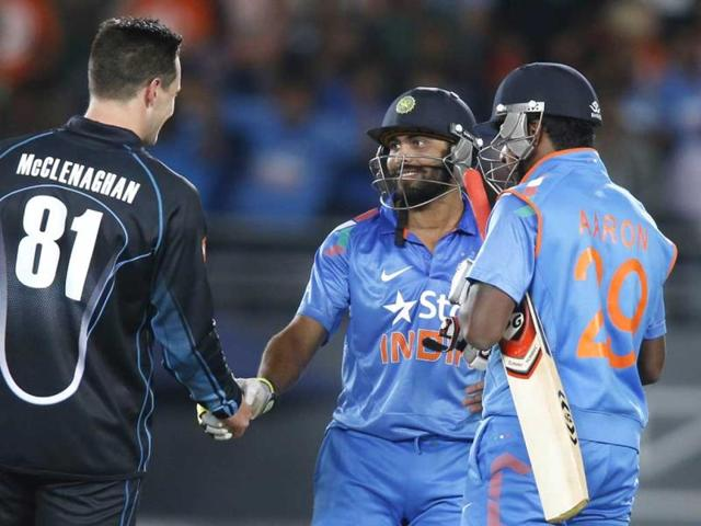 Ravindra Jajeda (C) and Varun Aaron (R) talk with Michell McClenaghan after drawing the third ODI at the Eden Park, Auckland. (AFP Photo)