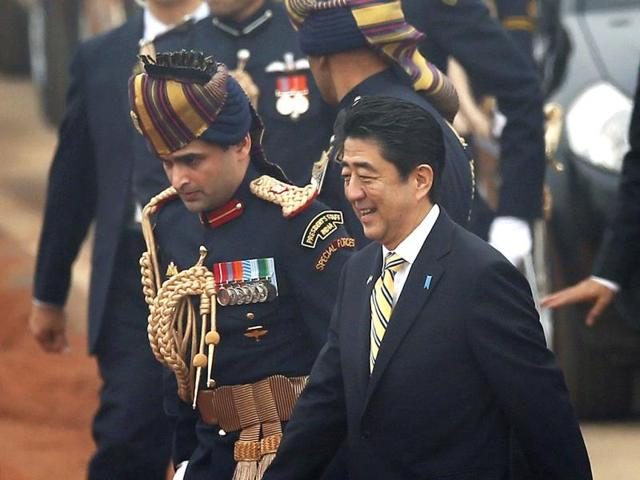 Japanese Prime Minister Shinzo Abe waves as he leaves along with President Pranab Mukherjee, center, after watching the Indian Republic Day parade as the chief guest in New Delhi, India. AP Photo