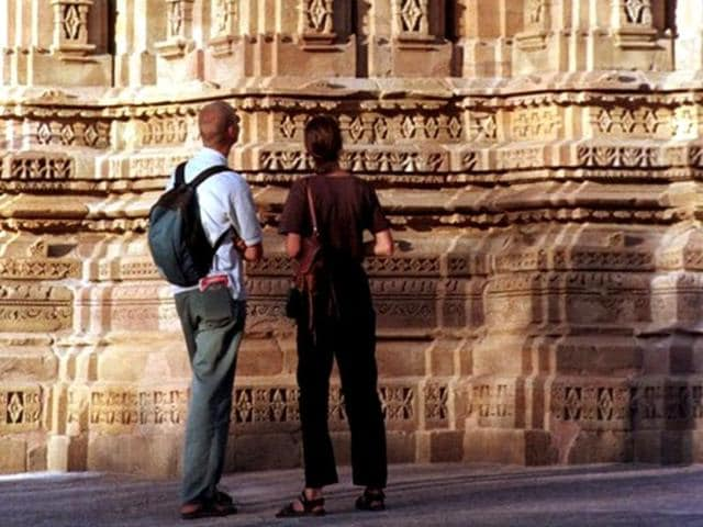 Two-foreign-tourists-take-a-look-at-sculptures-adorning-a-temple-at-the-Khajuraho-complex-built-in-the-tenth-century-under-the-Chandela-dynasty-AFP