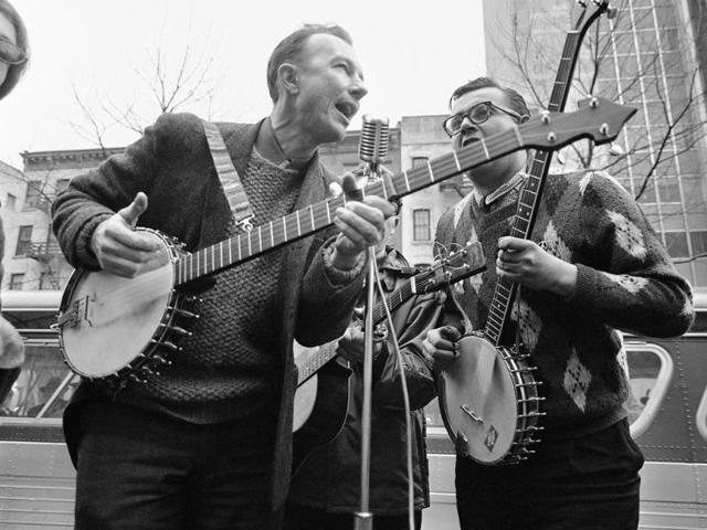 This file photo shows folk singer Pete Seeger, left, performing at the Rally for Détente at Carnegie Hall in New York.