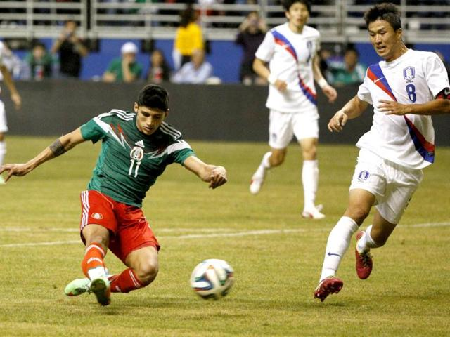 Mexico midfielder Alan Pulido scores a goal as Korea Republic midfielder Lee Ho defends during the second half in a friendly football match at Alamodome. (Reuters Photo)
