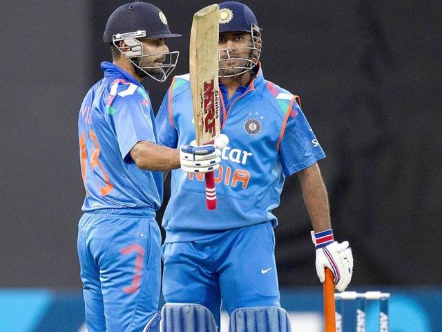 Virat Kohli (L) celebrates his half century (50 runs) with team mate MS Dhoni during the fifth and final ODI against New Zealand in Wellington. (AFP Photo)