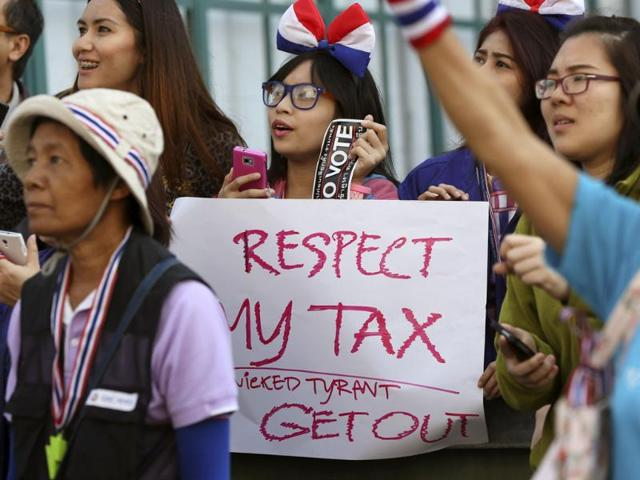 Thai office workers wait with a banner on the roadside to greet an anti-government protest leader during a march to encourage people not to take part in the upcoming election. (AP)