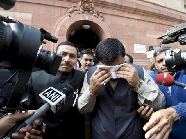 An unidentified member of Parliament, holding a handkerchief to his face leaves Parliament after protests inside the building. (AFP Photo)