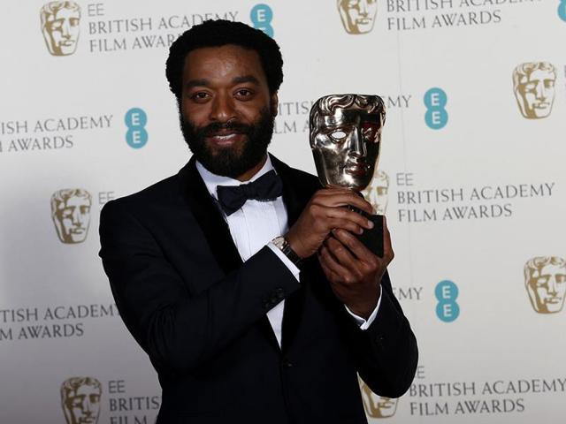Chiwetel-Ejiofor-nominated-for-best-actor-for-his-role-in-12-Years-a-Slave-with-Sari-Mercer-arrive-before-the-86th-Academy-Awards-at-the-Dolby-Theatre-in-Los-Angeles-March-2-2014-The-New-York-Times