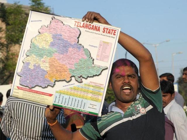A TRS supporter holds a map as he celebrates the planned creation of Telangana state in Hyderabad. (AFP photo)