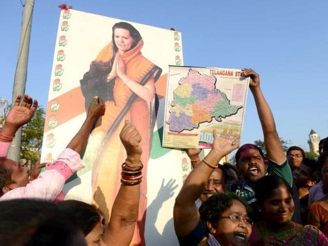 TRS supporters hold a hoarding of Congress president Sonia Gandhi as they celebrate the planned creation of Telangana state in Hyderabad. (AFP photo)