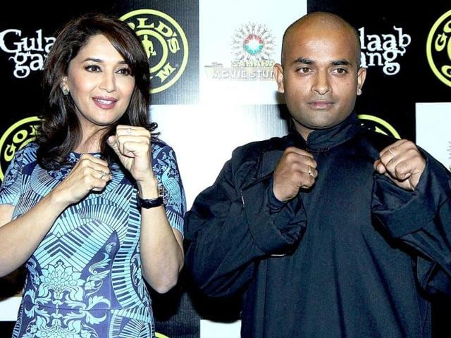 Madhuri Dixit with Kanishka Sharma (Shailon Martial Art expert) performs self defense techniques for women while promoting Gulaab Gang at a Gym in Bandra. (PTI Photo)