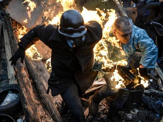 Protesters burn as they stand behind burning barricades during clashes with police in Kiev. (AFP photo)