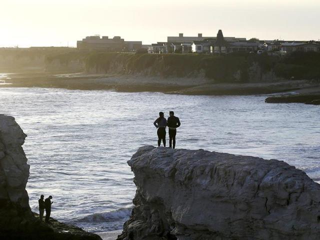 Visitors-watch-the-sunset-from-atop-the-bluffs-at-Natural-Bridges-State-Beach-in-Santa-Cruz-California-AP-Photo-Marcio-Jose-Sanchez