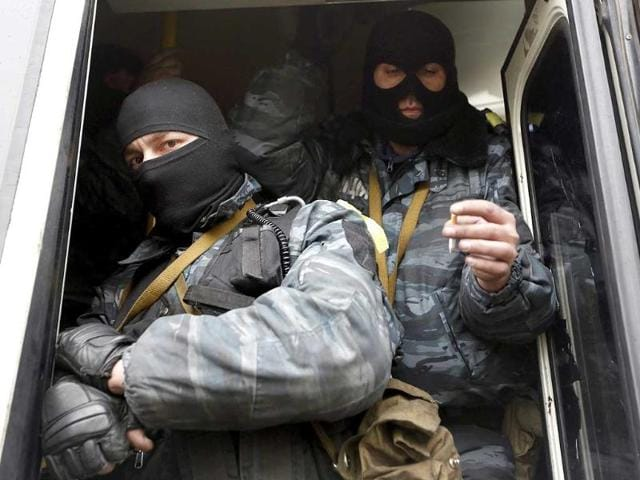 Members of Berkut anti-riot unit embark in a bus as they leave their barracks in Kiev. (Reuters Photo)
