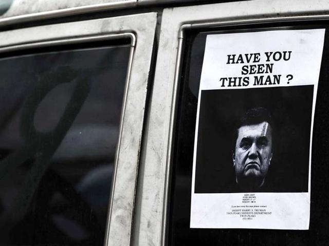 A-poster-showing-a-portrait-of-ousted-President-Viktor-Yanukovich-is-stuck-on-a-car-window-in-central-Kiev-on-February-24-2014-AFP-Photo