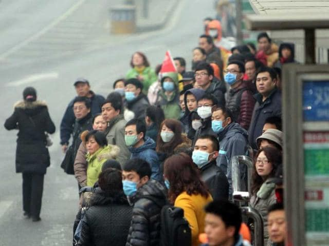 Picture shows residents waiting for buses in a bus station in haze-covered Beijing. (AFP photo)