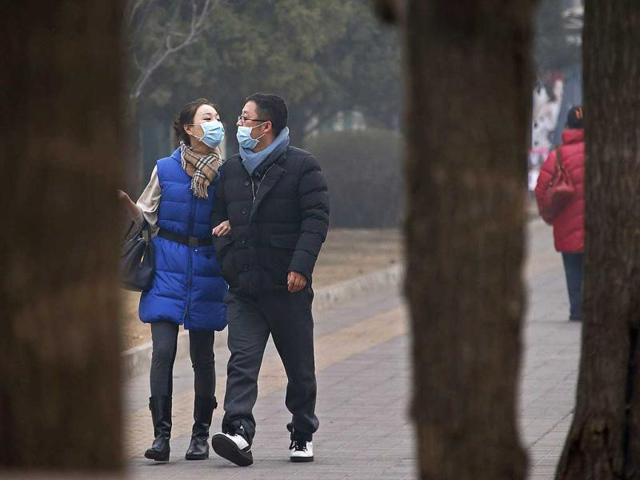 A couple wearing face masks walk along a street on a hazy afternoon in Beijing February 24, 2014. (Reuters Photo)