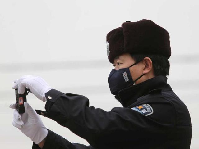 A policeman is seen wearing with a mask in smog-covered Beijing. China