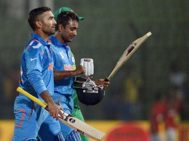 Dinesh Karthik (L) and Ambati Rayudu (R) walk off the field after winning the second match of the Asia Cup against Bangladesh at the Khan Shaheb Osman Ali Stadium in Fatullah. (AFP Photo)